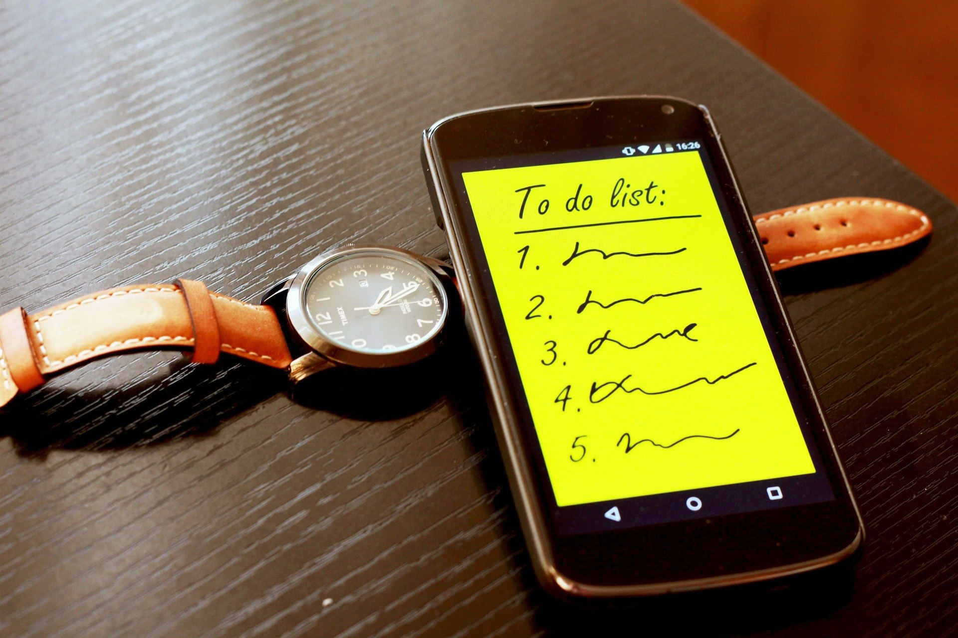 Cellphone with to do list written on it and a watch underneath