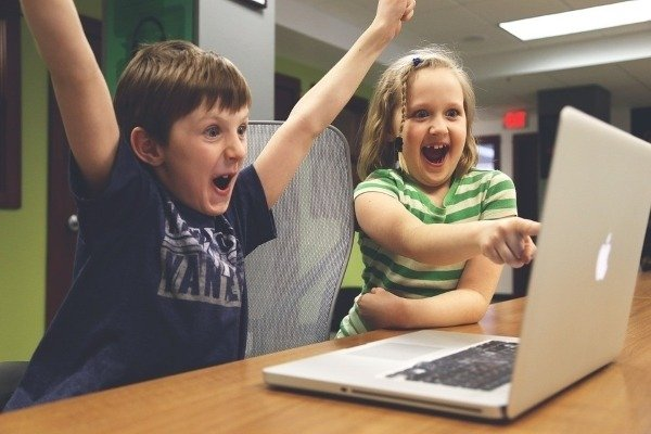 images of kids happily looking at laptop screen